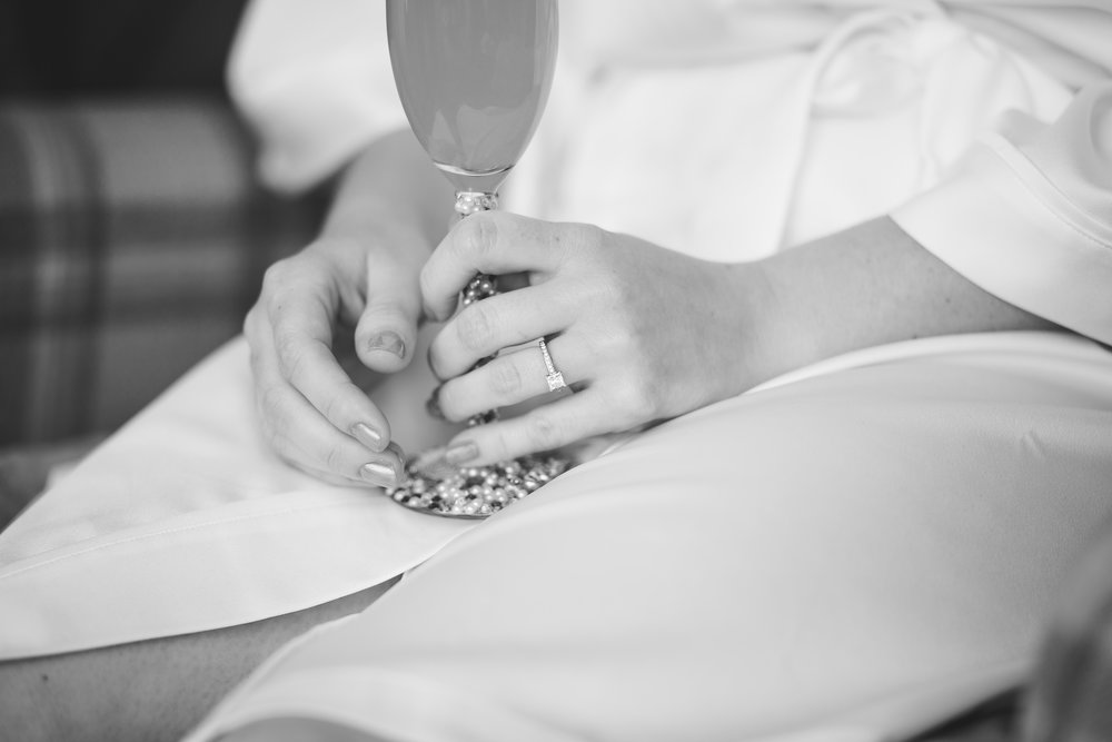 Black and white photograph of the bride holding a champagne glass- Documentary wedding photography