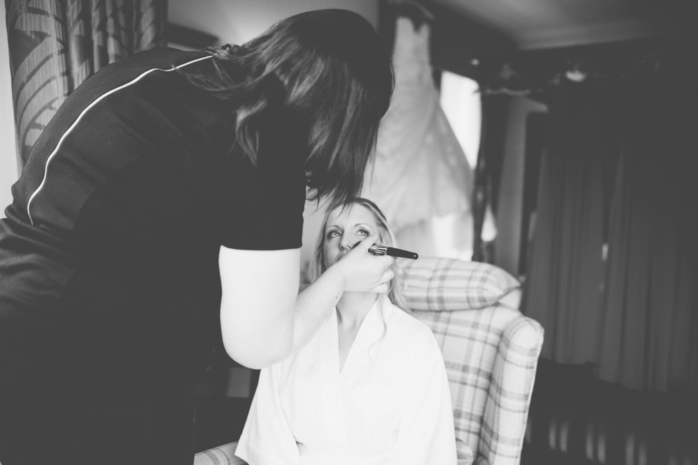 Black and white photograph of the bride getting makeup on for her wedding at Inn on the Lake- Documentary wedding photography