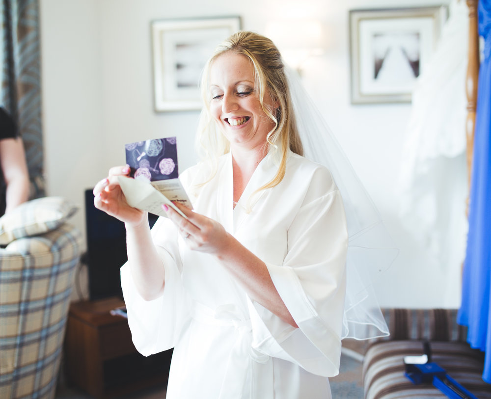 the bride opening her wedding cards- documentary wedding photography at Inn on the Lake