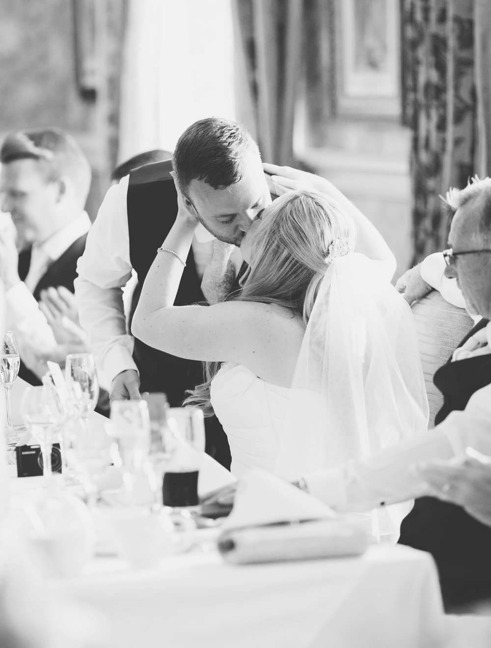 Black and white photograph of the bride and groom kissing- In the moment photography