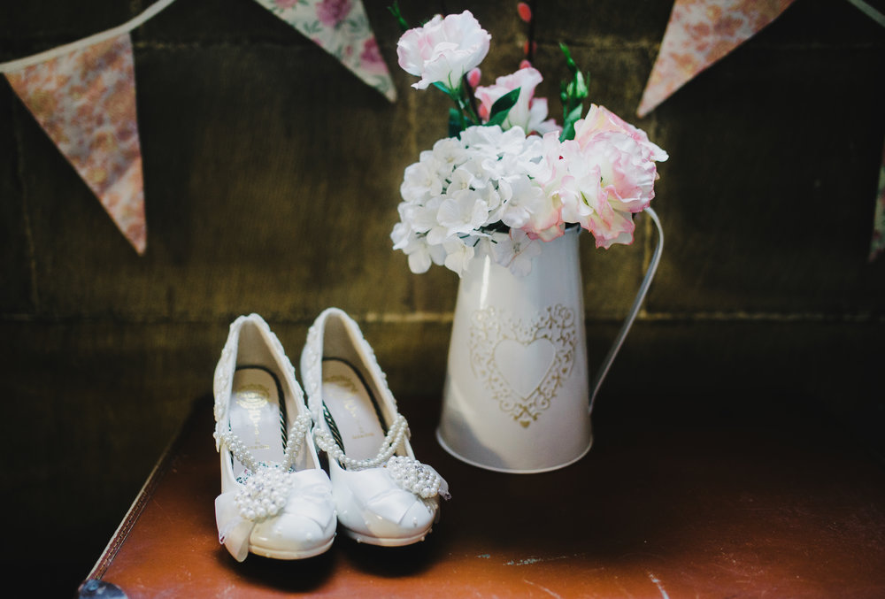 Bridal shoes with a watering can filled with flowers- Vintage themed wedding at Whalley Abbey