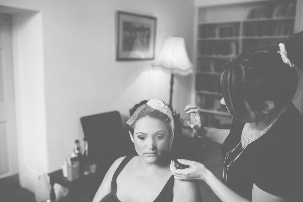 Black and white photograph of the bride getting her hair done- Documentary wedding photography of the bridal preparations