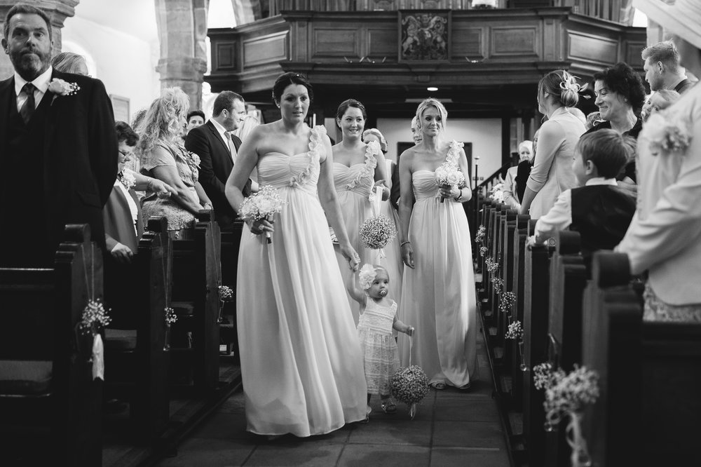 Black and white photograph of all of the bridesmaids walking down the aisle at Whalley Abbey- Ribble Valley wedding photographer