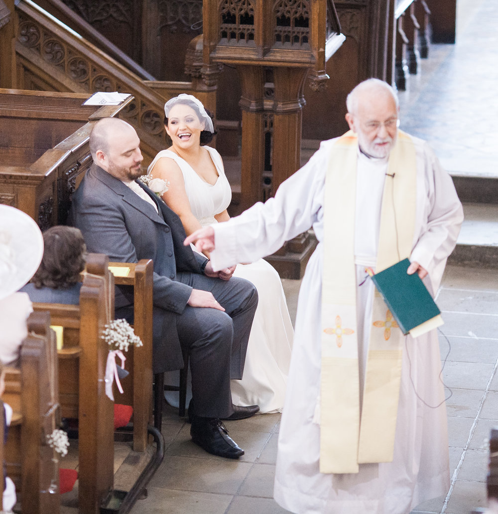 The bride smiling as she is sat next to the groom at the alter- Whalley Abbey for a rustic themed wedding