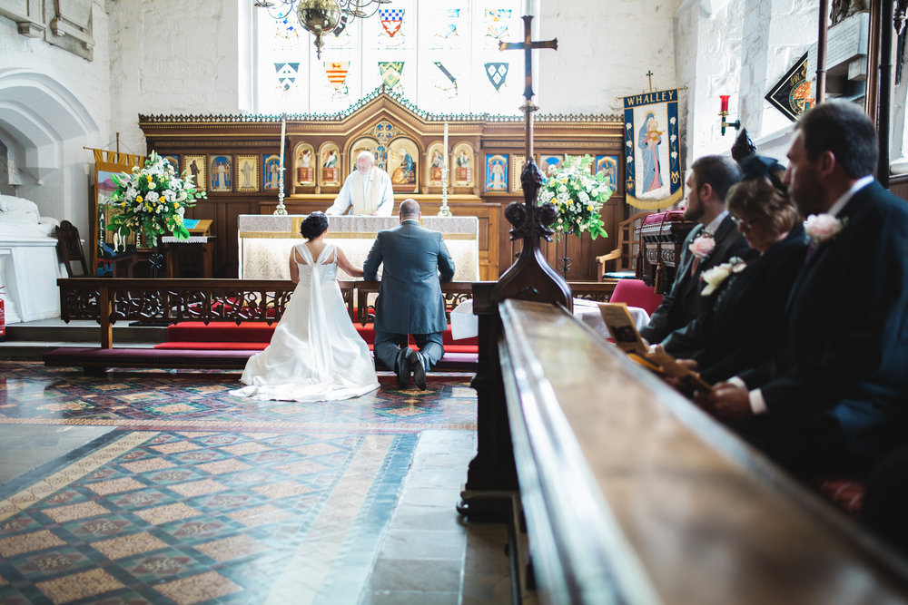 The bride and groom knelt at the alter- Documentary wedding styled photography