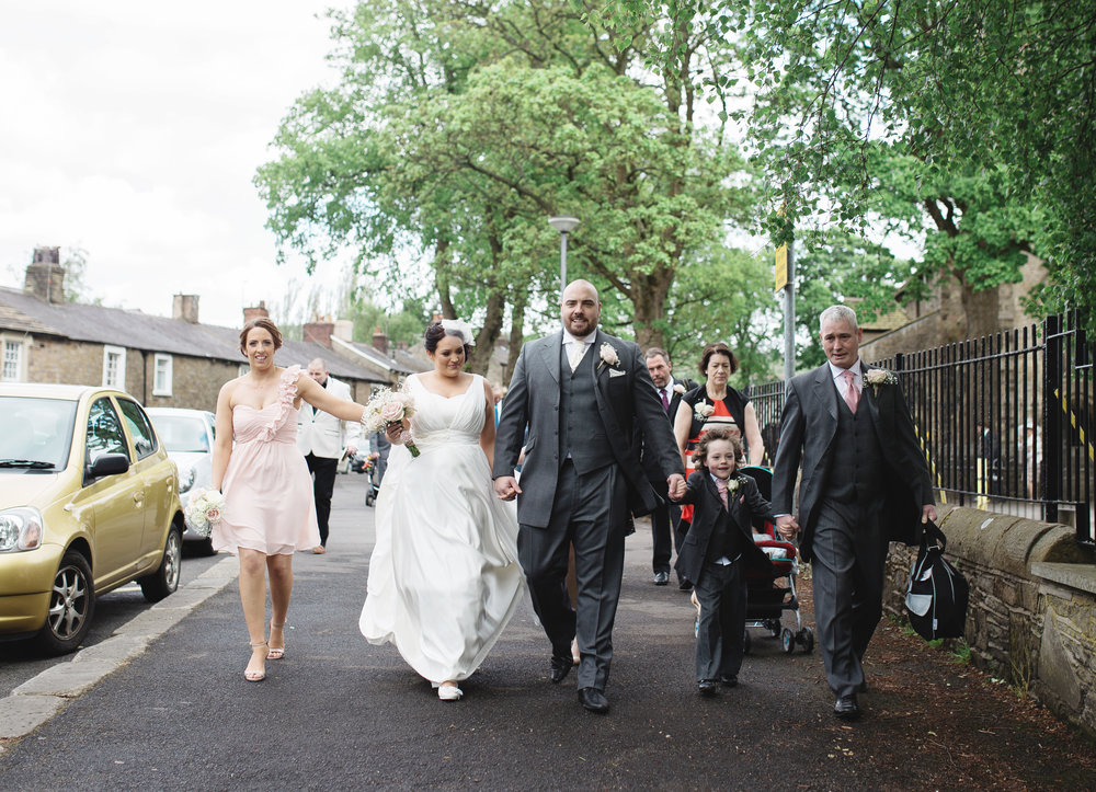 The bride and groom walking the streets of ribble valley along with their wedding guests- Documentary wedding photography