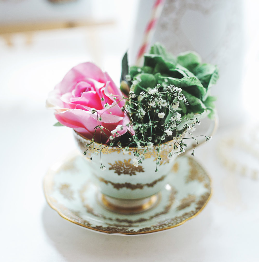 A rose in a tea cup for table arrangement - Rustic themed wedding in lancashire