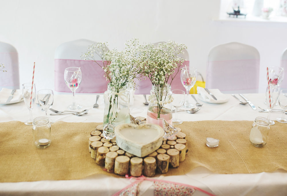 Flowers in a mason jar and a logged place mat -Rustic themed wedding table arrangements