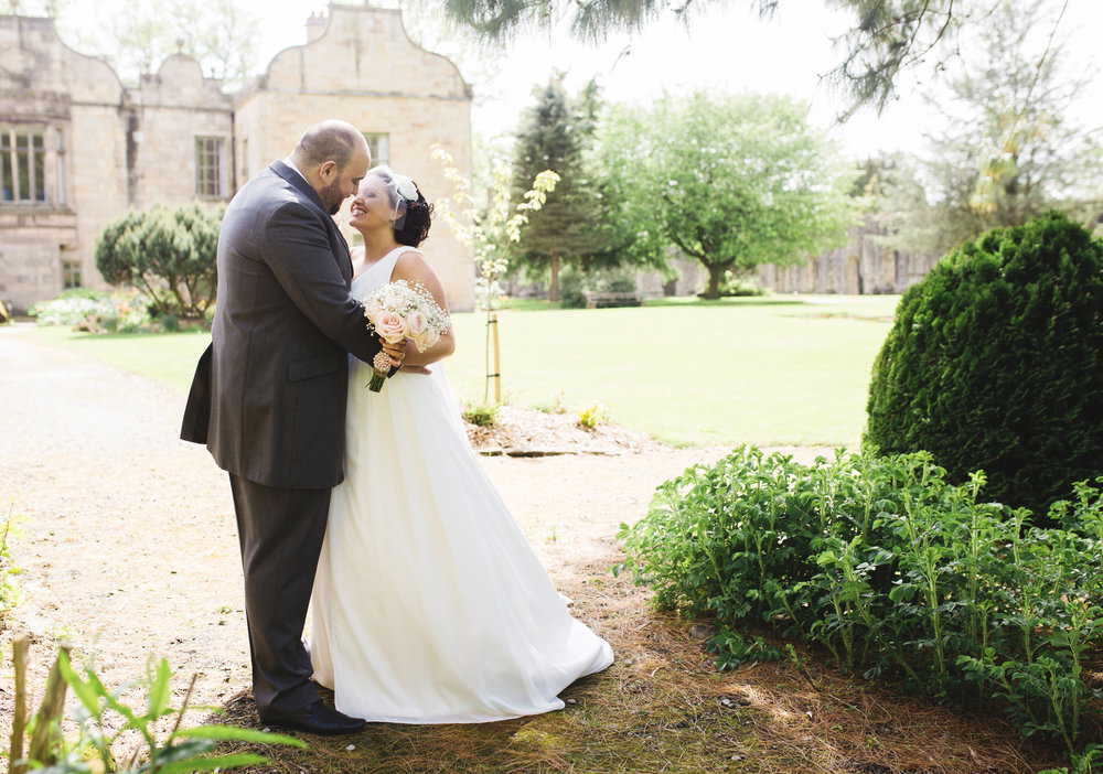 The bride and groom kissing in front of Whalley Abbey in ribble valley- creative wedding photographer in lancashire