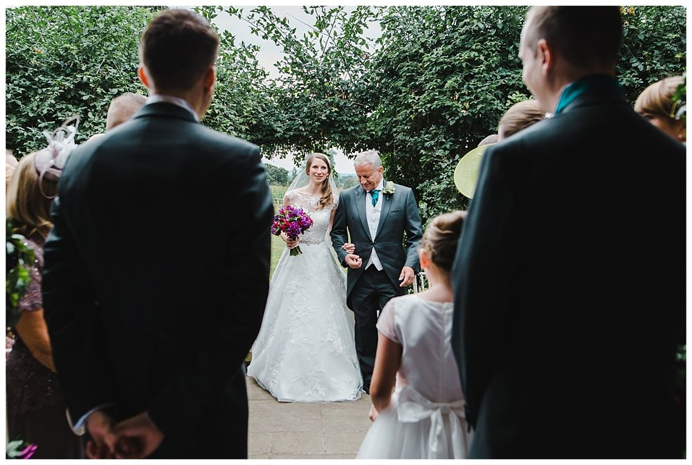 bride walking down the aisle with her father as the groom waits at the alter- Creative wedding photography in cheshire