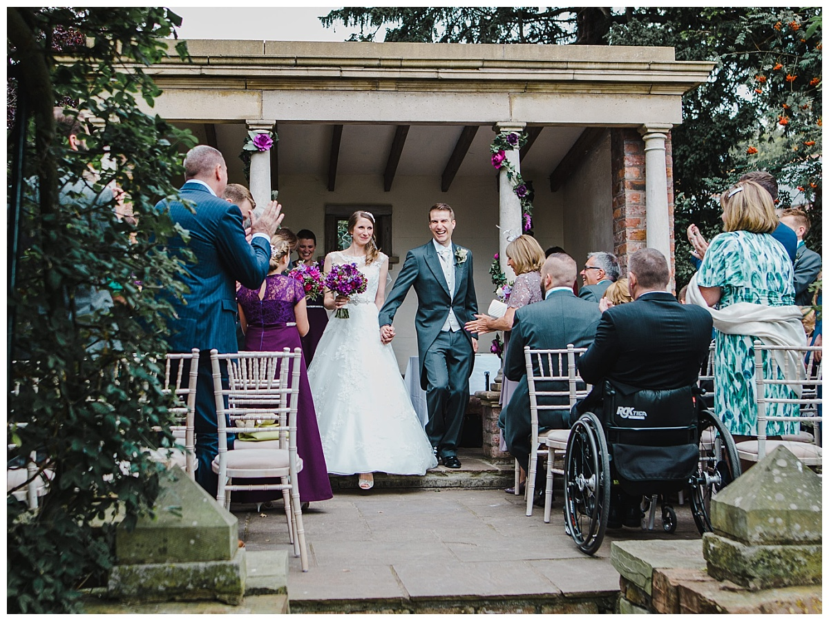 Just married! bride and groom walk down the aisle at Cheshire wedding
