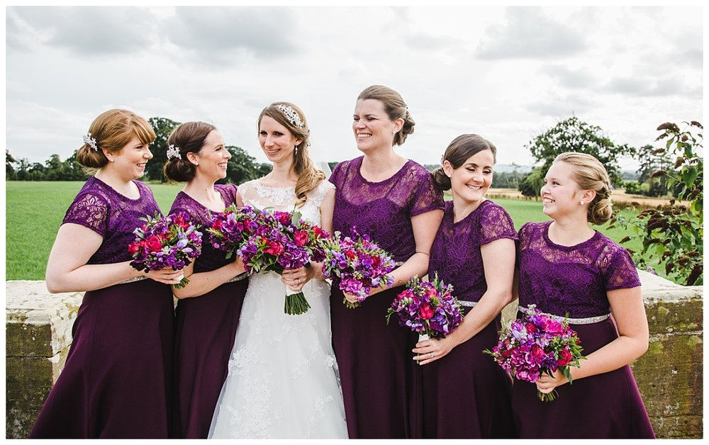 The bride and all of the bridesmaids holding their flowers- Creative wedding photography outside of Willington Hall Hotel