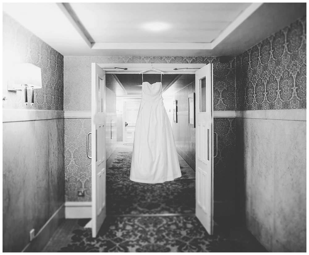 The wedding dress hung up in the hall way- Manchester wedding photographer, black and white