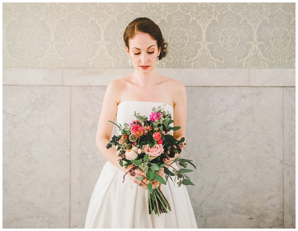 The bride looking down at her pink flower bouquet- Bridal portraiture at manchester town hall