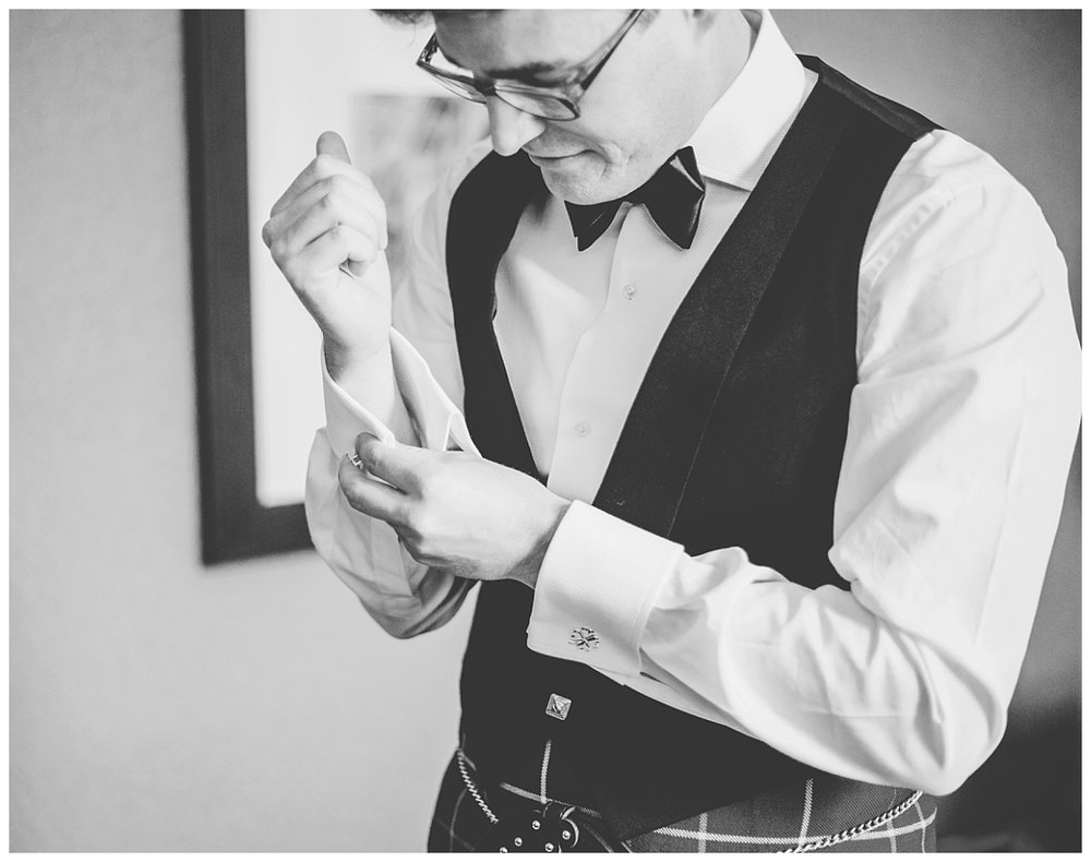 Black and white wedding photography of the groom putting on his cuff links- Documentary wedding photography in manchester town hall
