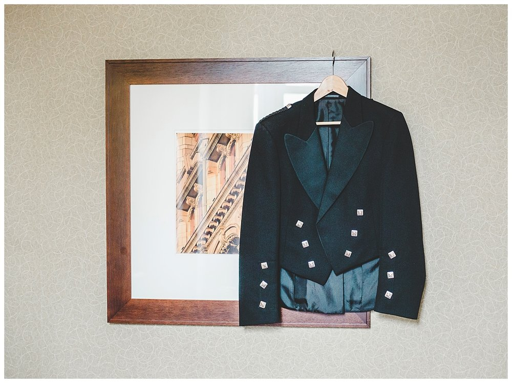 The grooms suit hung on a picture frame- Creative wedding photography