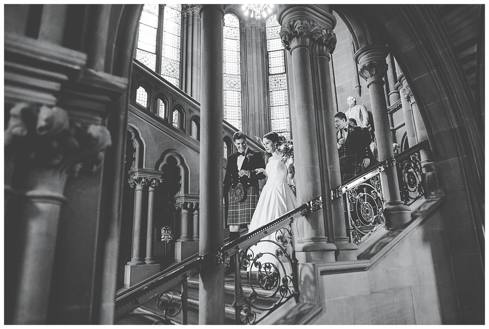 Bride and groom walk down the steps at Manchester Town Hall - documentary wedding photography in Manchester
