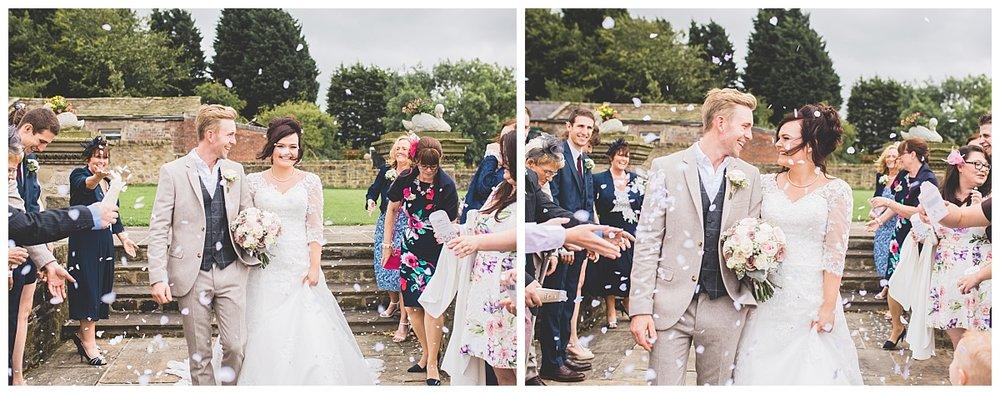 The bride an groom walking through confetti air- Creative wedding photography at Beeston Manor