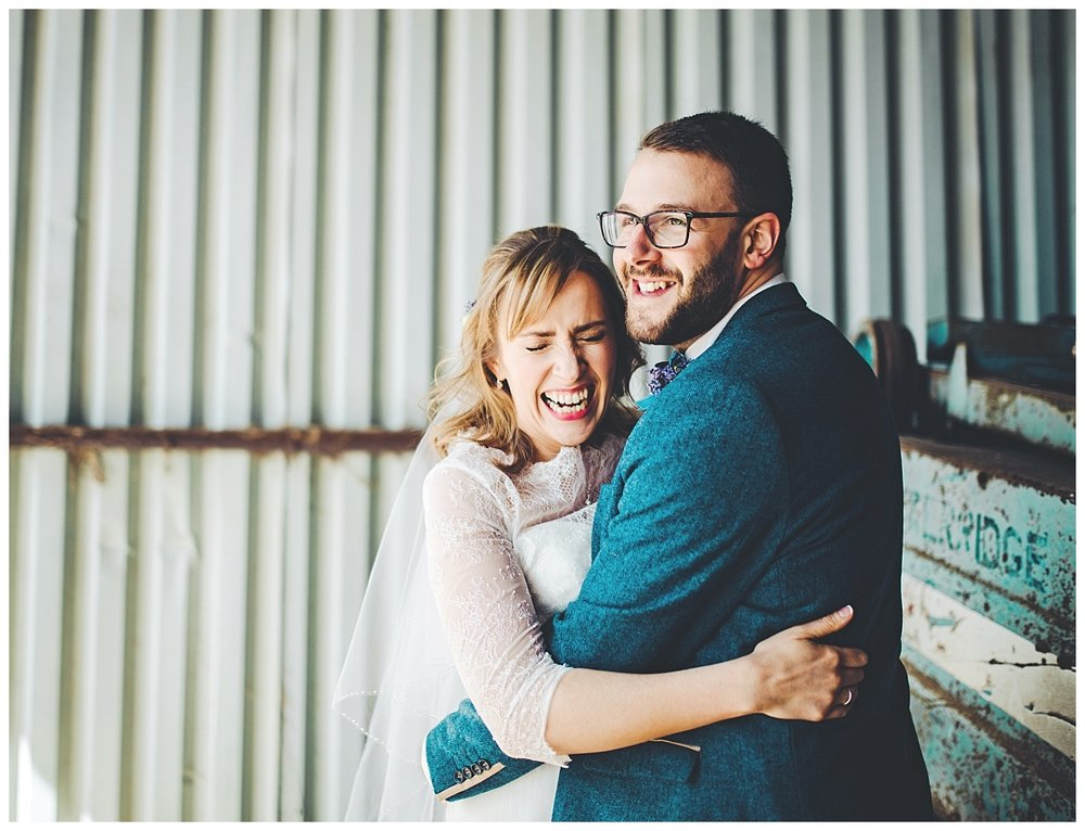 bride and groom embrace and laugh - wedding photography in Cheshire