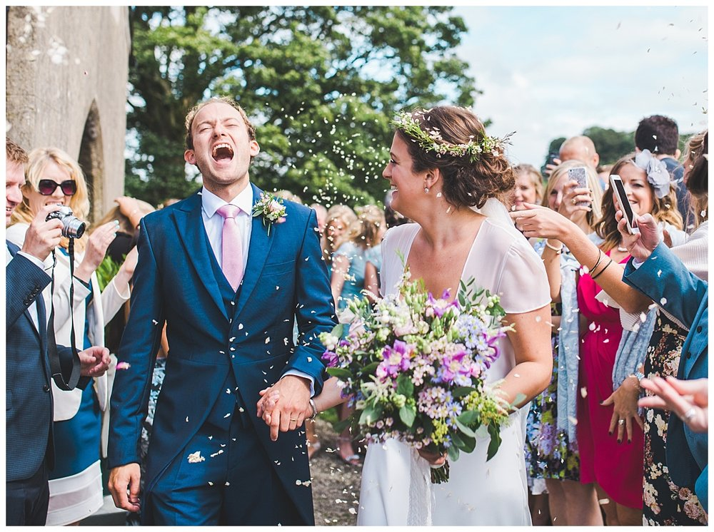bride and groom walk through confetti - modern and relaxed wedding photography in the ribble valley