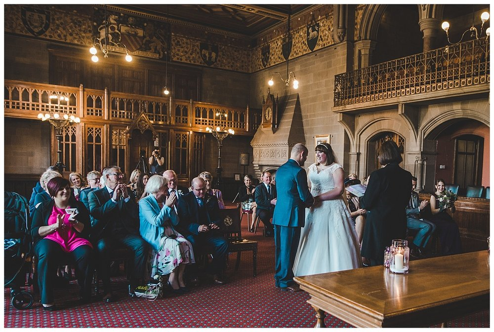 bride and groom exchange wedding rings - documentary wedding photographer in manchester
