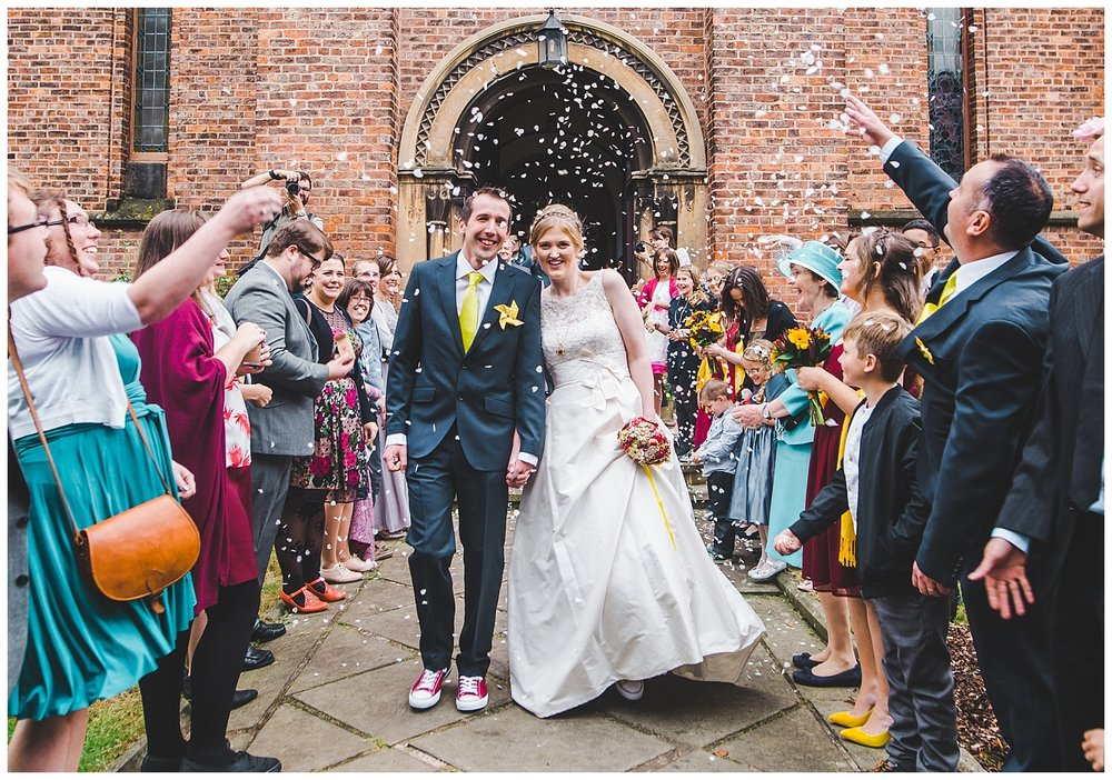 bride and groom walking through the confetti - church in manchester