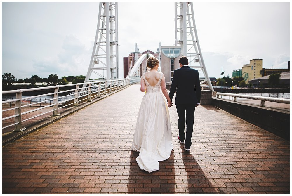 bride and groom walking across the bridge in Manchester