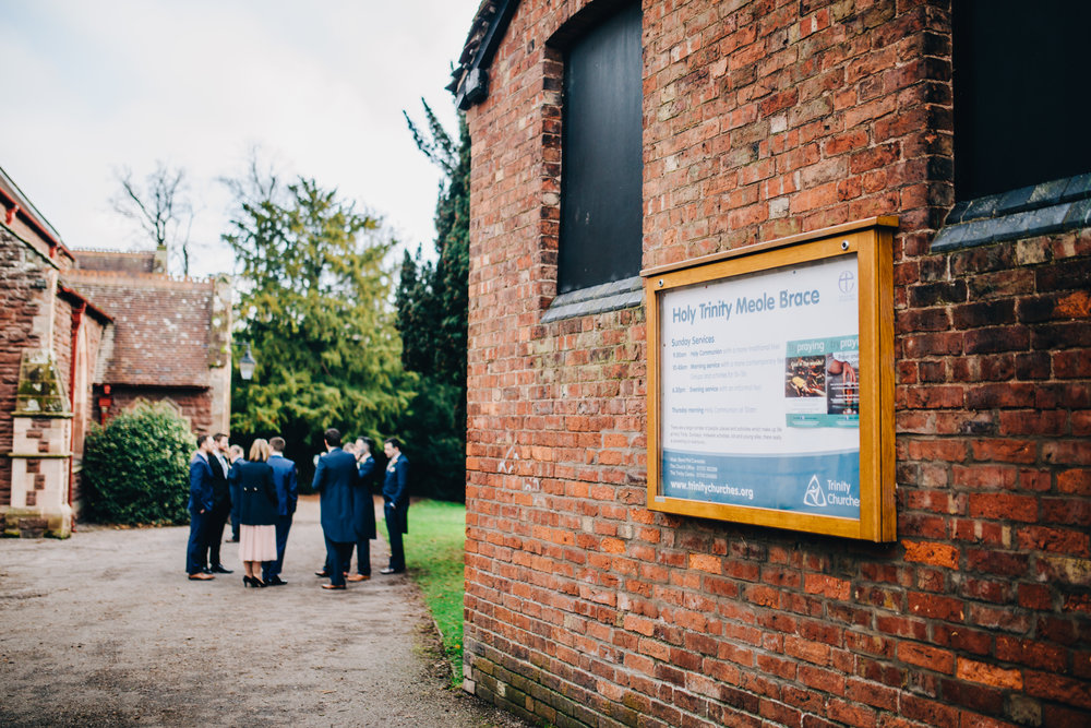 groom and groomsmen wait outside church - wedding photographer in the north west