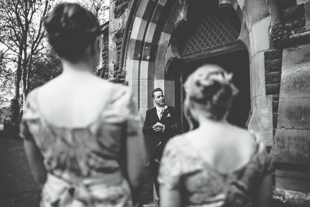 black and white wedding photography - guests chat outside church