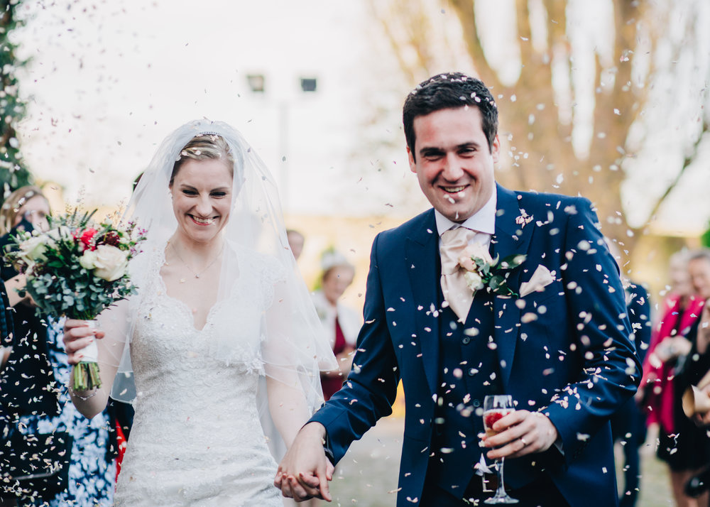 close up shot of bride and groom walking through the confetti - laughter and emotion in wedding pictures
