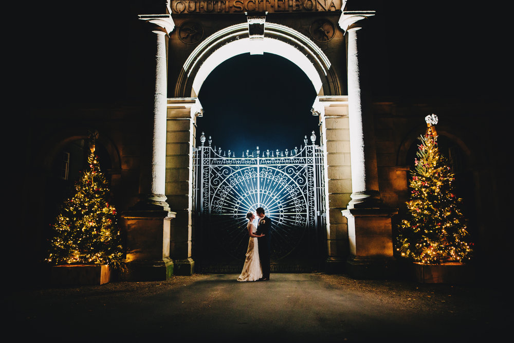 epic winter wedding pictures - back lit flash image - bride and groom outside gates