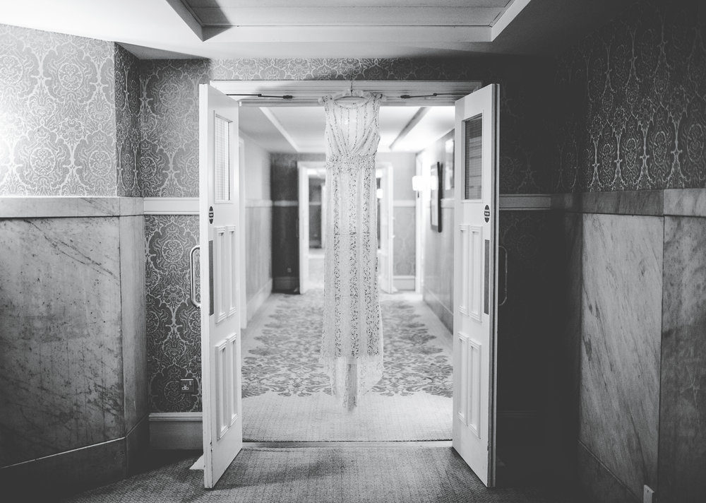 bride's dress hangs in the hall way of a manchester hotel