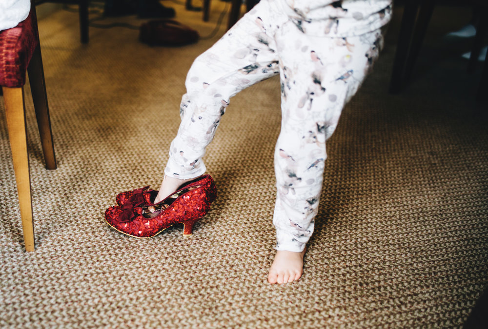 little girl tries on mums shoes - documentary wedding images