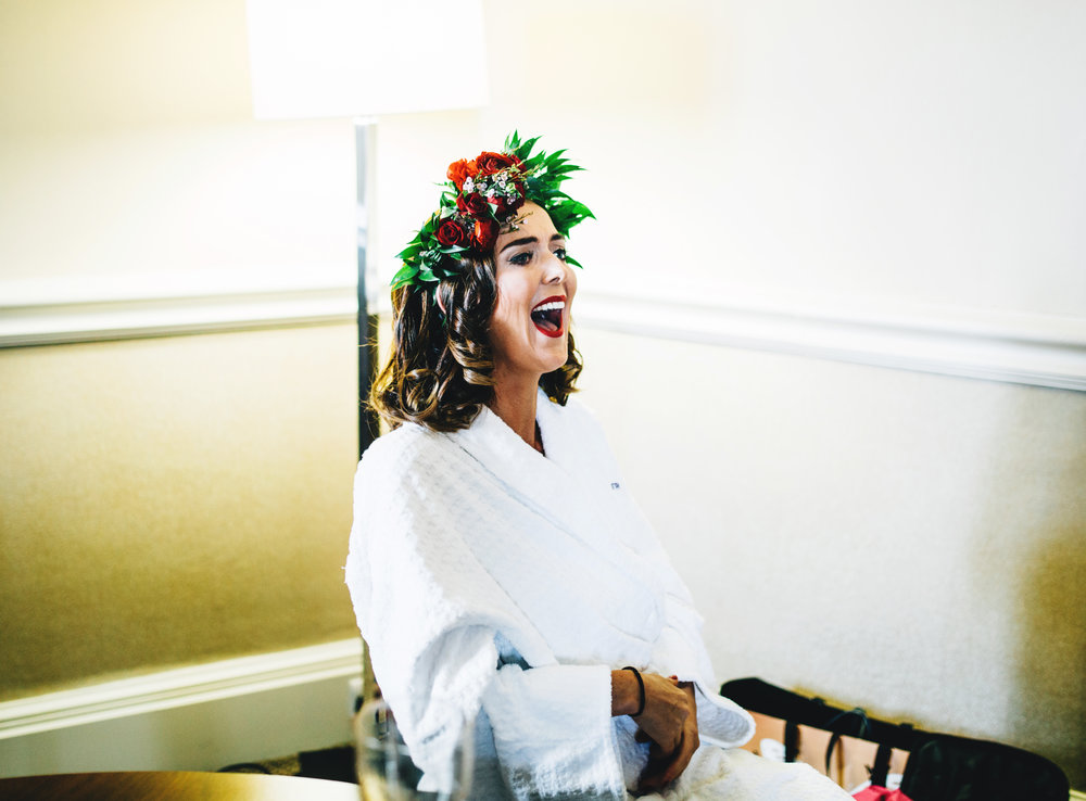 natural image of bride laughing as she gets ready for her wedding
