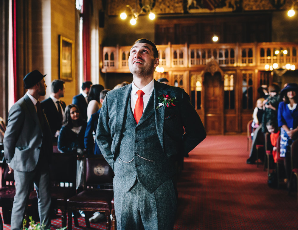 groom showing emotion as he waits for bride to arrive at manchester town hall wedding