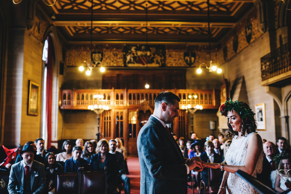 creative images at manchester town hall wedding - bride and groom exchanging rings.