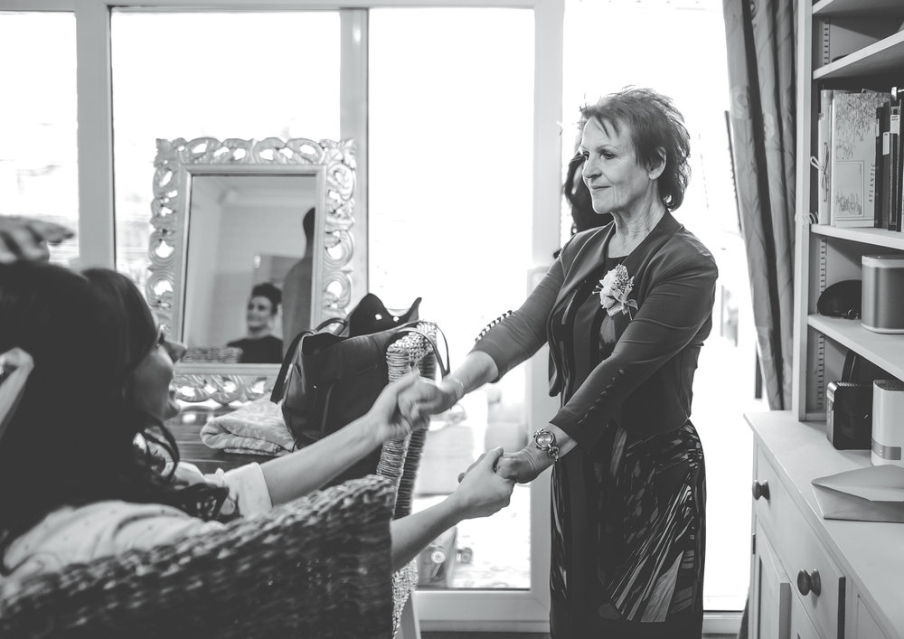 bride holds hands with her step mum during emotional moment - wedding photographer in manchester