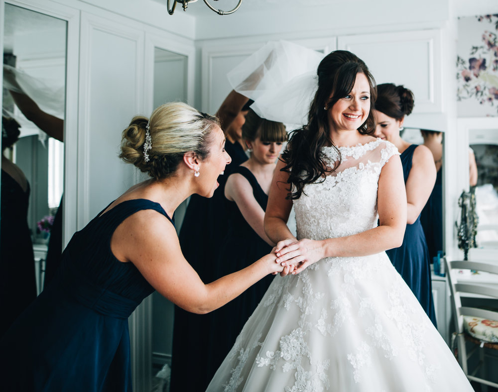 bride getting dressed surrounded by her bridesmaids - manchester wedding photography