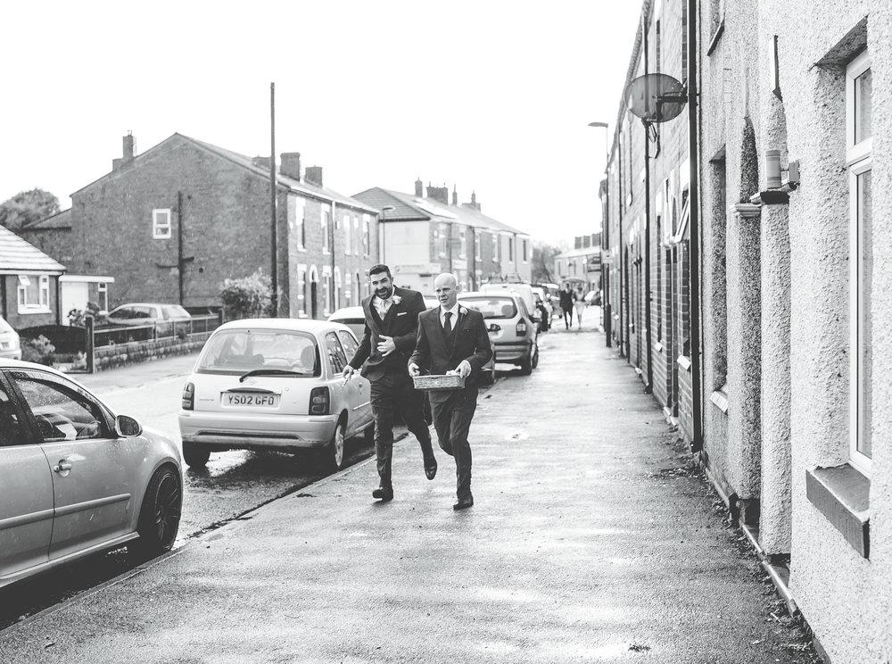 groom and best man run through the rain - creative documentary photography in manchester