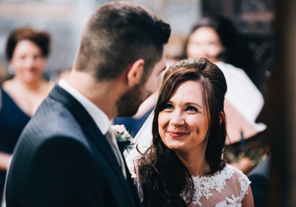 bride and groom smile at each other.