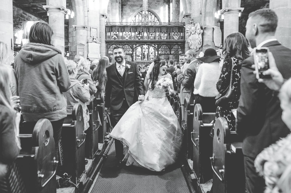 black and white photography - bride and groom walking down the aisle