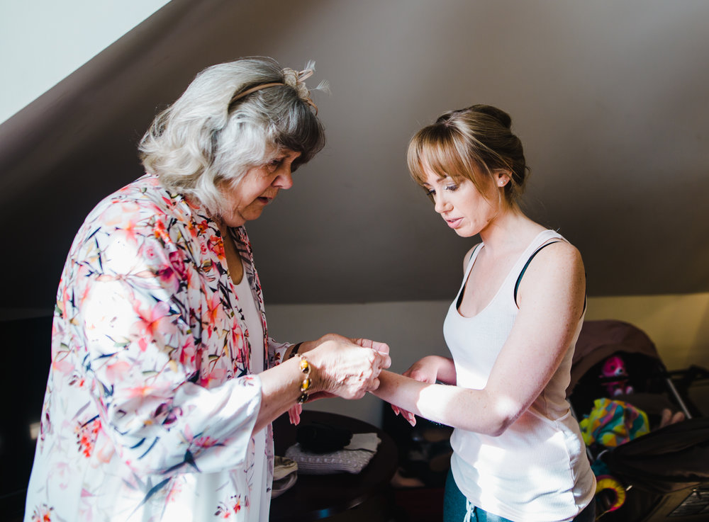 bride's grandma gives bride a bracelet to wear on the wedding day - documentary wedding photography in Lancashire