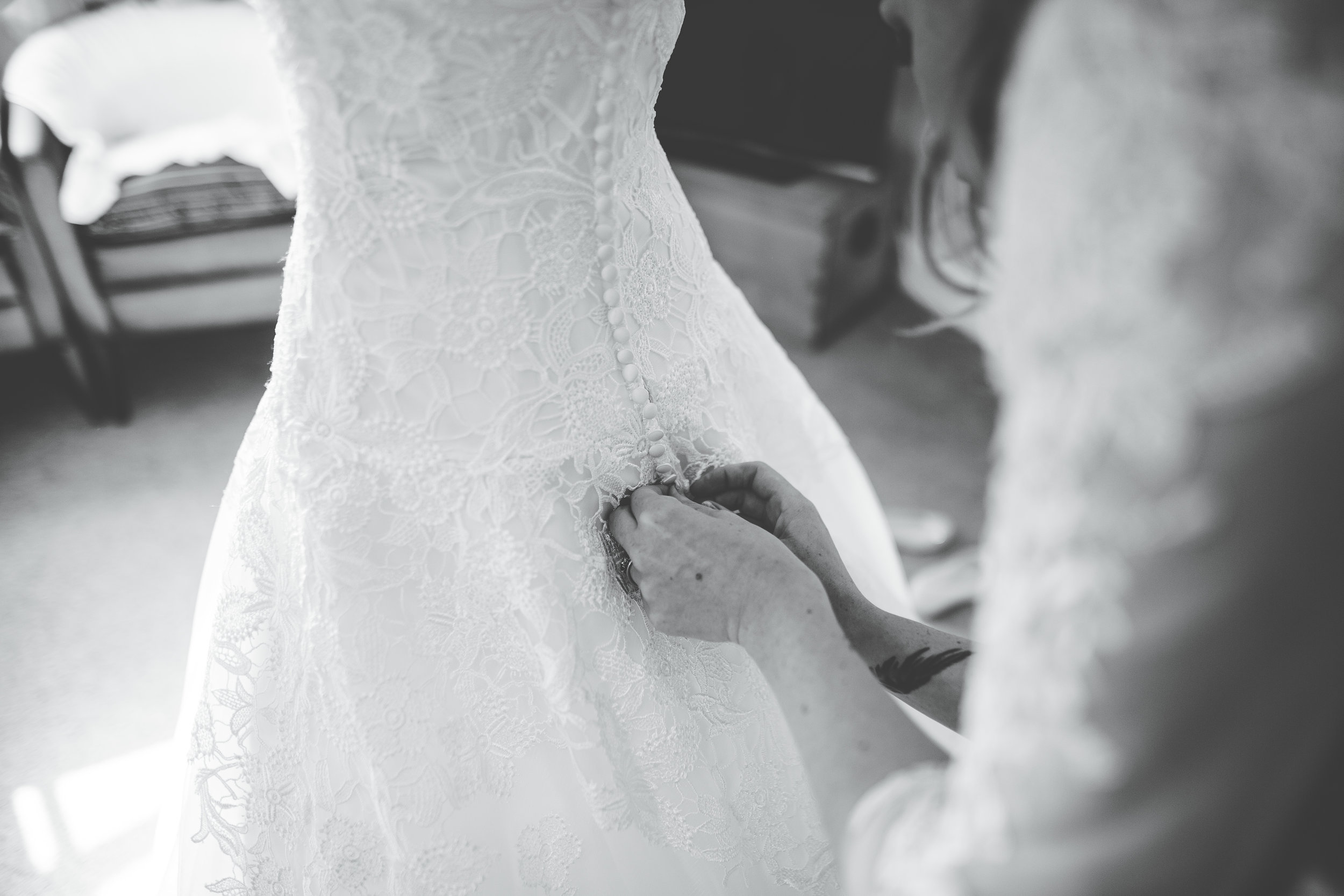 dress being fastened. - black and white wedding photography