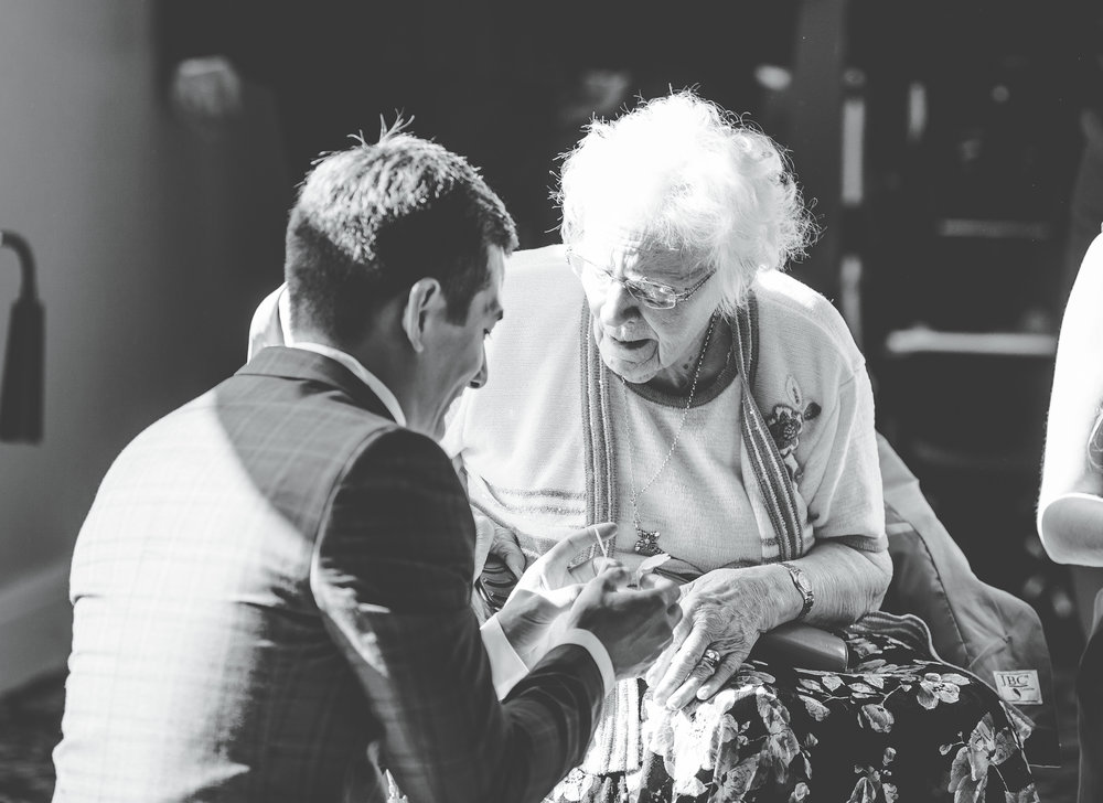 groom sits with his grandmother - wedding photography in Lancashire