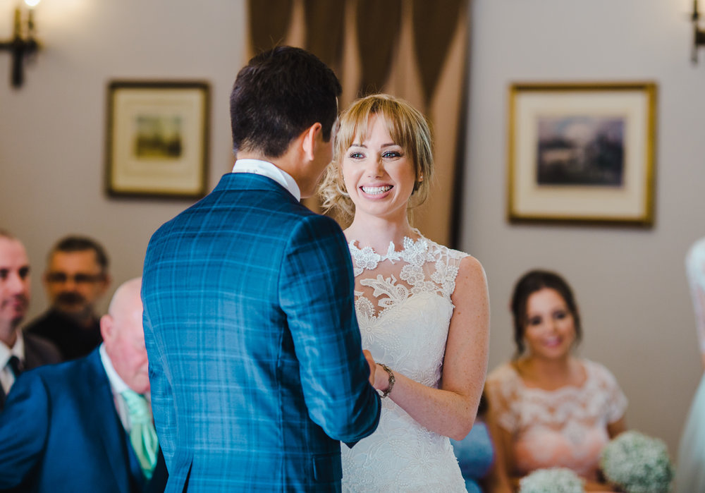 colour image of the bride and groom exchanging wedding rings - wedding photos from the Villa at Wrea Green
