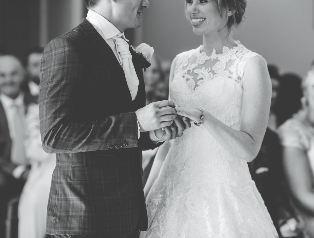 close up of bride and groom exchanging rings - black and white wedding photographs