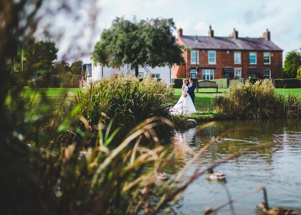 The villa at wrea green wedding photography - bride and groom by the pond