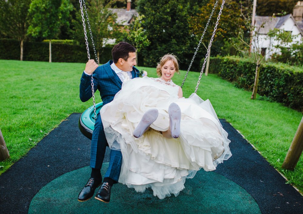 couple play in the swing - fun and modern wedding pictures