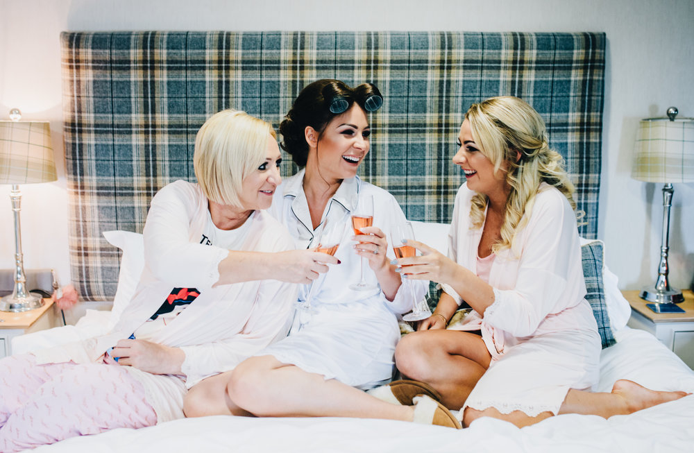 bride laughs and smiles with her mother and sister - natural documentary style wedding photography in Lancashire