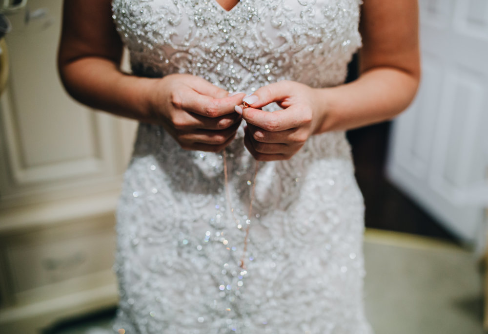 bride holds a necklace in her hands